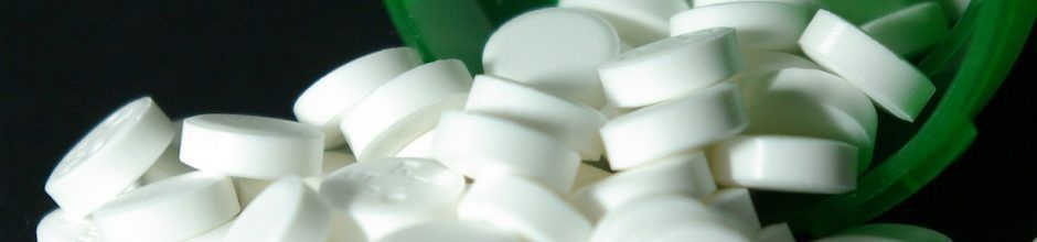 Pills spilling out of green bottle