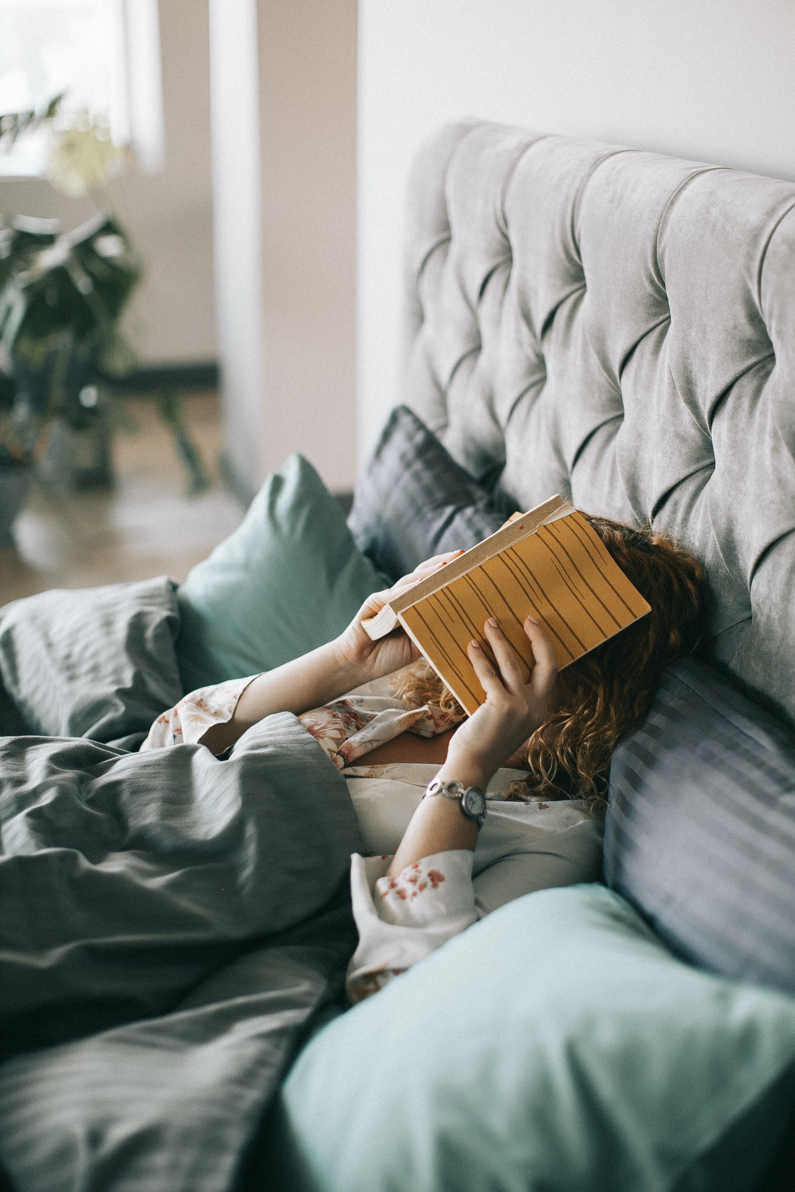 Woman in bed with book on her face