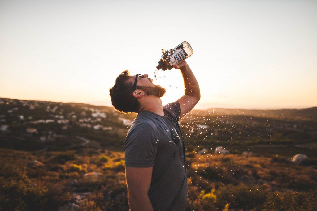 Man drinking water against the sunset