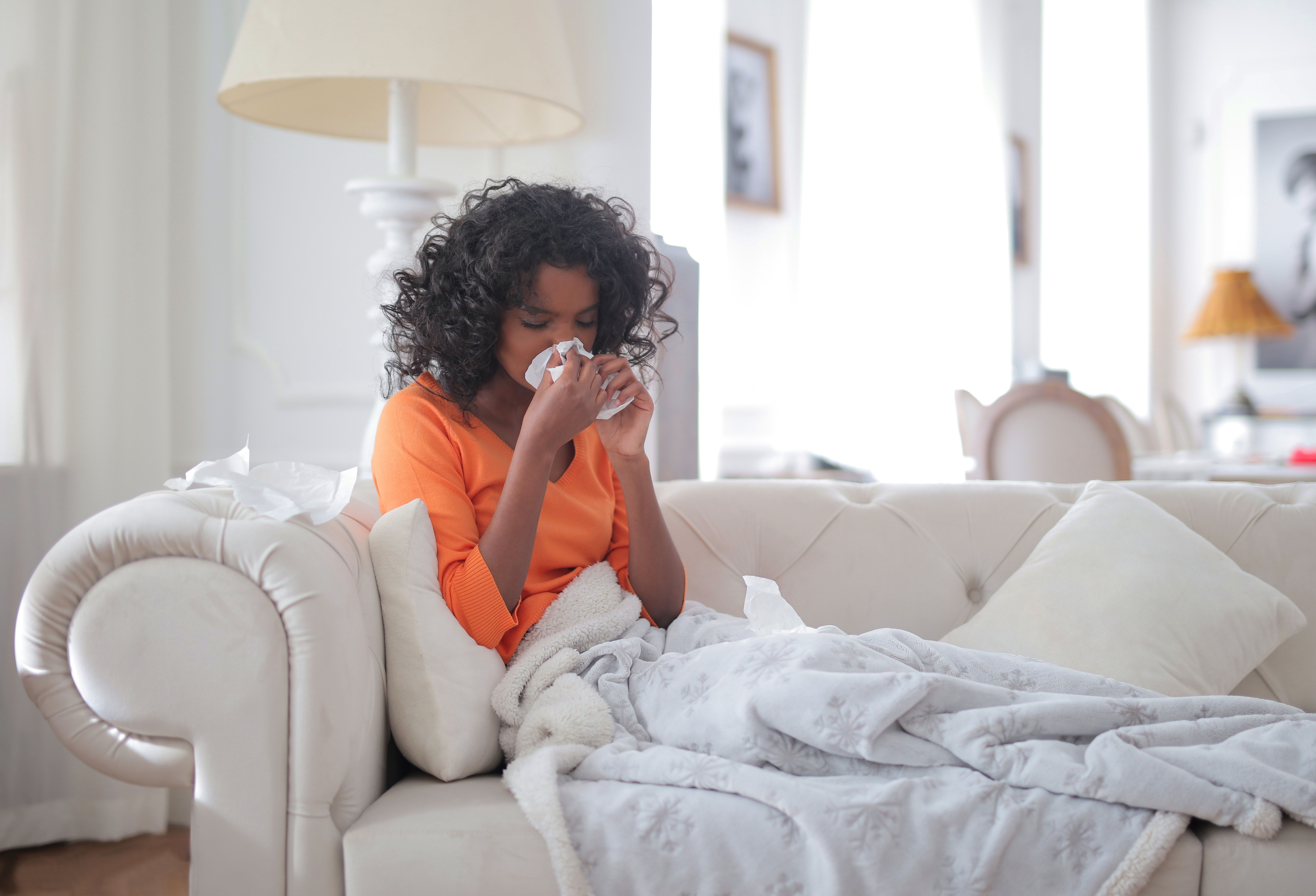 Woman on the couch with a congested nose